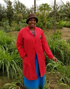 Anne Nderit in a red jacket and brown hat smiling at her farm in Gilgil, Kenya
